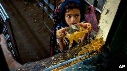 اسلام آباد، ایک پاکستانی لڑکی بری امام مزار کے قریب مفت کھانا وصول کرتے ہوئے۔