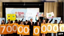 Tổng thư ký Liên hiệp quốc Ban Ki-moon (giữa) đứng cùng các học sinh trường Nest+m ở New York cầm các tấm bảng ghi dân số thế giới lên đến 7 tỉ vào ngày 31/10/11
