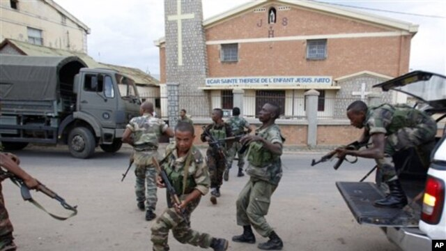 Government military officers run outside the air force base near the airport in Antananarivo, Madagascar, 20 Nov 2010