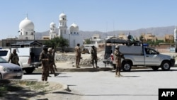 FILE - Pakistani soldiers stand guard at the site where two Chinese missionaries was kidnapped in the neighborhood of Jinnah town in Quetta on May 24, 2017.