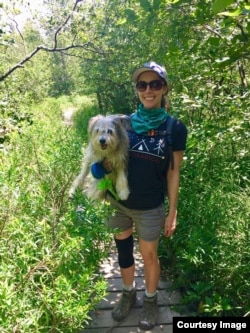 Ashley Thompson of VOA Learning English holds her dog Dublin as they hike trails together in West Virginia. (Photo Courtesy of Ashley Thompson)
