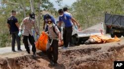 Polisi dan tim penyelamat melakukan penguburan massal korban tewas gempa dan tsunami di Palu.