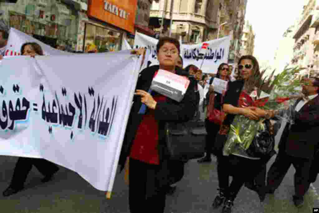 "Egyptian women carry banners in Arabic that read:""Social justice,"" as they march to Cairo's central Tahrir Square to celebrate International Women's Day, Tuesday, March 8, 2011. A protest by hundreds of Egyptian women demanding an end to sexual harassment"