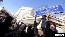 Warga Iran melakukan protes atas eksekusi terhadap ulama Syiah Nimr Al-Nimr di depan Kedutaan Arab Saudi di Teheran, Minggu (3/1).
