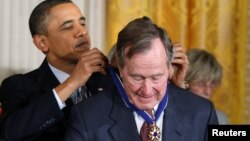 Tổng thống Mỹ Barack Obama đeo Huân chương Tự do cho cựu Tổng thống George H.W. Bush trong một buổi lễ tại NHà Trắng ở Washington, ngày 15 tháng 2, 2011.