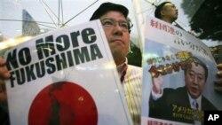 """Seorang pengunjuk rasa menyuarakan protes anti PLTN-nya dengan memegang kertas bertuliskan """"No More Fukushima"""" dan sebuah potret PM Jepang Yoshihiko Noda di Tokyo, Sabtu (15/12)."""