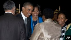 President Barack Obama and first lady Michelle Obama are greeted upon their arrival at Waterkloof Air Base in Centurion, South Africa, June 28, 2013,.