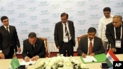 Sahatmurad Mamedov dari Turkmengaz, kiri, dan Bhuwan Chandra Tripathi dari BUMN India Gail Ltd., saat menandatangani kesepakatan kerjasama, Avaza, Turkmenistan, 23 Mei 2012. (Foto: dok.)