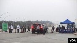 Kendaraan yang membawa para anggota parlemen melewati pos pemeriksaan gedung parlemen Birma di Naypyitaw, Senin (31/1).