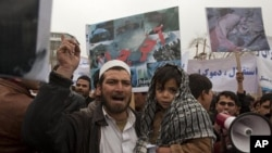 An Afghan man and his son take part in a protest in Kabul, March 6, 2011