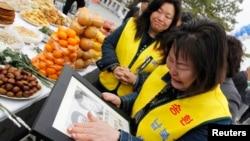 지난 2011년 4월 비무장 지대 인근 임진각에서 납북 희생자 추모 행사가 열린 가운데, 한국의 납북자 가족이 사진을 들고 울고 있다. (자료사진)
