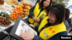 지난 2011년 한국 비무장 지대 인근 임진각에서 납북자 추모 행사가 열린 가운데, 납북 희생자 가족들이 사진을 들고 울고 있다. (자료사진)