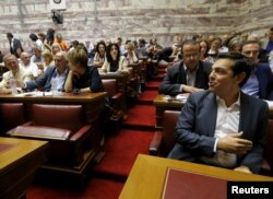 Greek Prime Minister Alexis Tsipras (R) is seen before a ruling Syriza party parliamentary group session in Athens, Greece July 15, 2015.