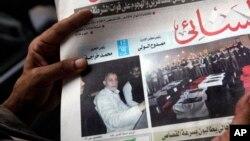 一名埃及人在开罗举着报道穆斯林兄弟会精神领袖巴迪被捕的报纸(2013年8月20日)