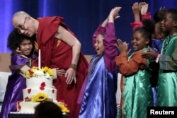 A group of children celebrate with the Dalai Lama after he blew out a candle on his birthday cake at the University of California, Irvine on July 6, 2015.