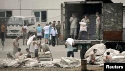 지난 2010년 중국 단둥 시와 마주보는 북한 신의주 압록강 인근에서 북한 인부들이 중국산 밀가루를 트럭에 싣고 있다. (자료사진)