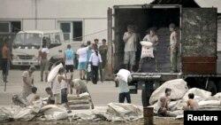 지난 2010년 중국 단둥시와 마주보는 북한 신의주 압록강 인근에서 북한 인부들이 중국산 밀가루를 트럭에 싣고 있다.