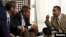 Peter Maurer, center, president of the International Committee of the Red Cross, listens to Hamid al-Awadhi, right, undersecretary of Yemen's Foreign Ministry, upon arrival at the international airport of Yemen's capital, Sana'a, August 8, 2015.