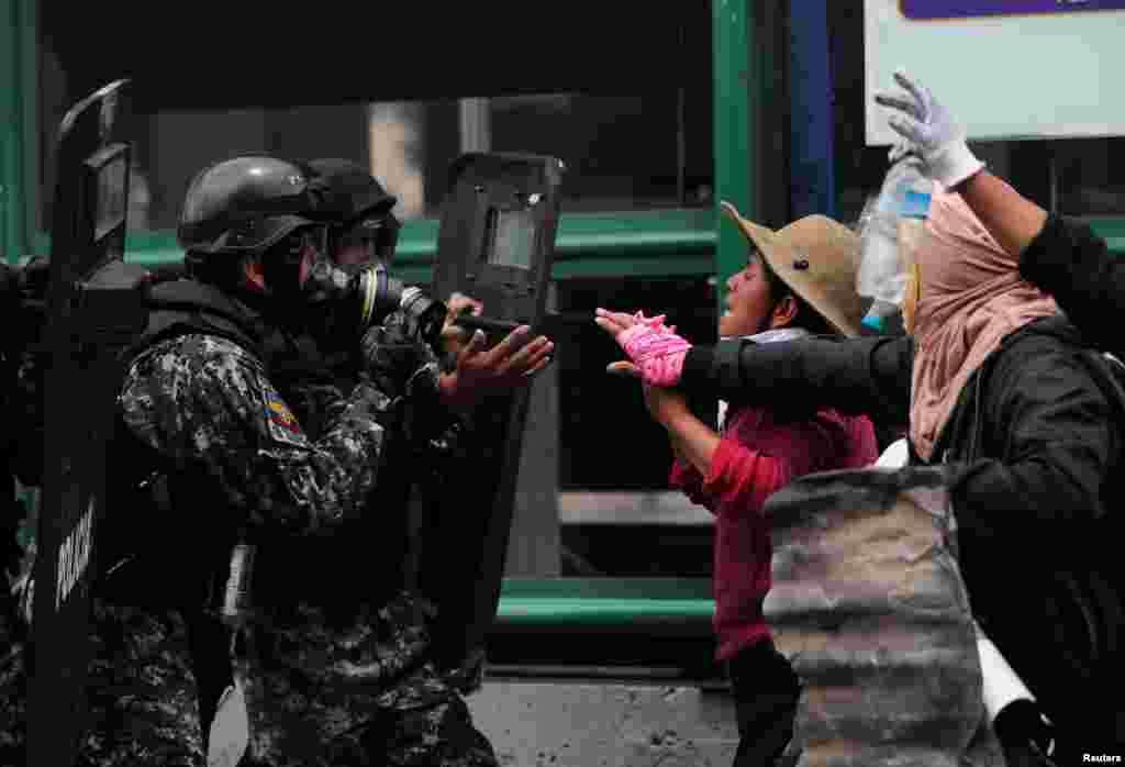 Demonstrators face security forces during a protest against Ecuador's President Lenin Moreno's austerity measures in Quito, Ecuador.