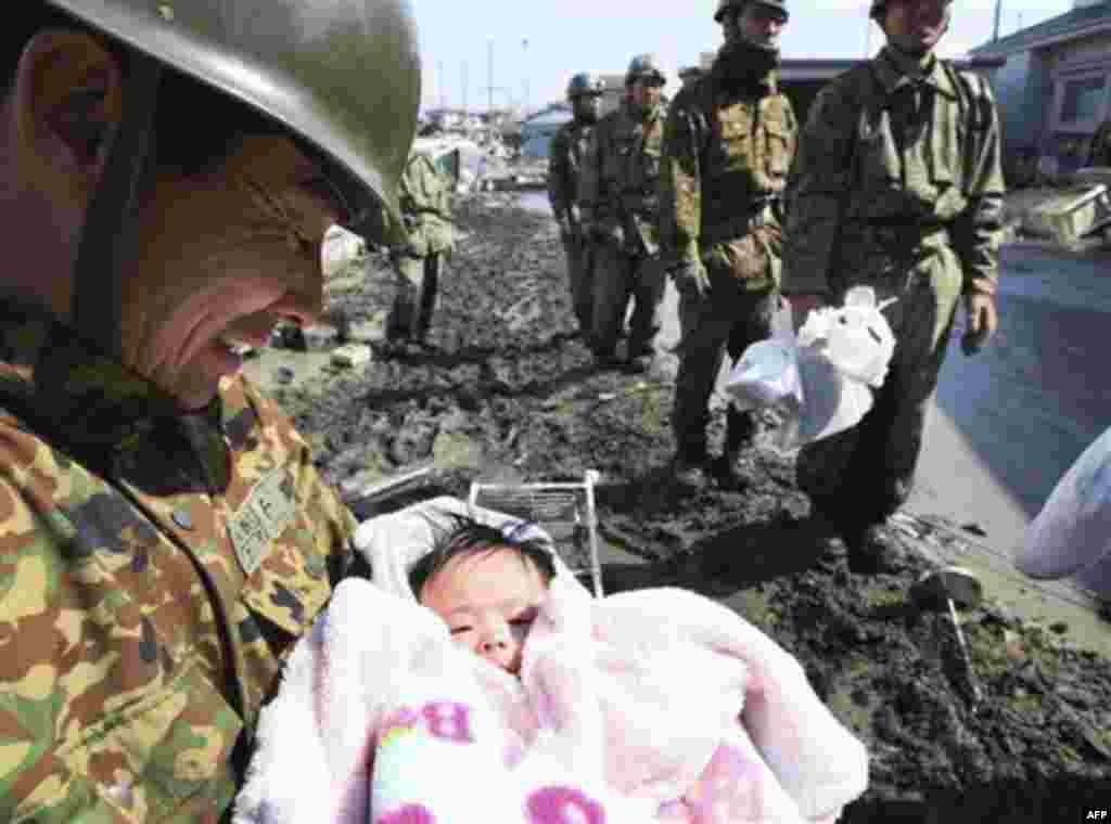 A Japan Self-Defense Force member reacts after rescuing a four-month-old baby girl in Ishinomaki, northern Japan, Monday, March 14, 2011, three days after a powerful earthquake-triggered tsunami hit the country's east coast. (AP Photo/The Yomiuri Shimbun,
