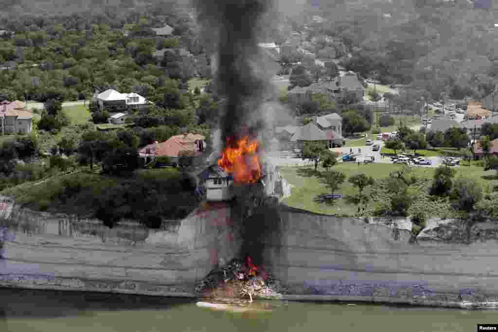 Smoke rises from a house deliberately set on fire, days after part of the ground it was resting on collapsed into Lake Whitney, Texas, June 13, 2014. Building crews set fire to the luxury lake house left dangling about 75 feet (23 meters) on a decaying cliff that has been giving way underneath the structure.