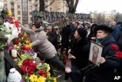 People place flowers to pay their respect at a memorial dedicated to people who died in early 2014 in clashes with security forces in central Kyiv during mass protests that ousted pro-Russia president Viktor Yanukovych, at Independence Square (Maidan) in Kyiv, Ukraine, Feb. 20, 2019.