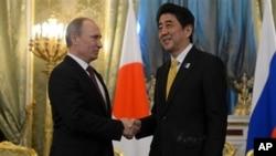 Presiden Rusia Vladimir Putin berjabat tangan dengan PM Jepang Shinzo Abe setibanya di Kremlin, Moskow (29/4).