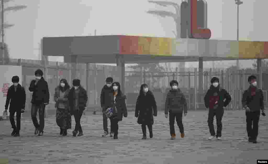 Japanese tourists wearing masks make their way to the Olympic Park amid thick haze in Beijing, Feb. 25, 2014.