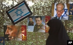 A woman walks past anti-Israel posters depicting Israel's President Shimon Peres, Defense Minister Ehud Barak and a caricature of Prime Minister Benjamin Netanyahu (L-R) as she visits a war exhibition held by Iran's revolutionary guard, at Baharestan squa