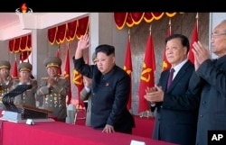 FILE - In an image made from video, North Korean leader Kim Jong Un, center, and Liu Yunshan, China's Communist Party's No. 5 leader, second right, waves during a ceremony in Pyongyang.