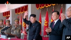 In an image made from video, North Korean leader Kim Jong Un, center, and Liu Yunshan, China's Communist Party's No. 5 leader, second right, waves during a ceremony to mark the 70th anniversary of the country's ruling party, in Pyongyang, Oct. 10, 2015. (KRT via AP Video)