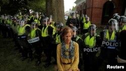 """Una manifestante parada frente a oficiales de policía del estado de Virginia que forman un cordón en la Universidad de Virginia, antes del primer aniversario de las protestas de Charlottesville 2017 """"Unite the Right"""", en Charlottesville, Virginia, el 11 de agosto de 2018."""