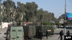 Polisi anti huru hara Mesir mengelilingi pintu masuk Universitas Al-Azhar saat bentrok dengan siswa yang mendukung Ikhwanul Muslimin, di distrik Nasr City, Timur Kairo, pada tanggal 27 Desember 2013.