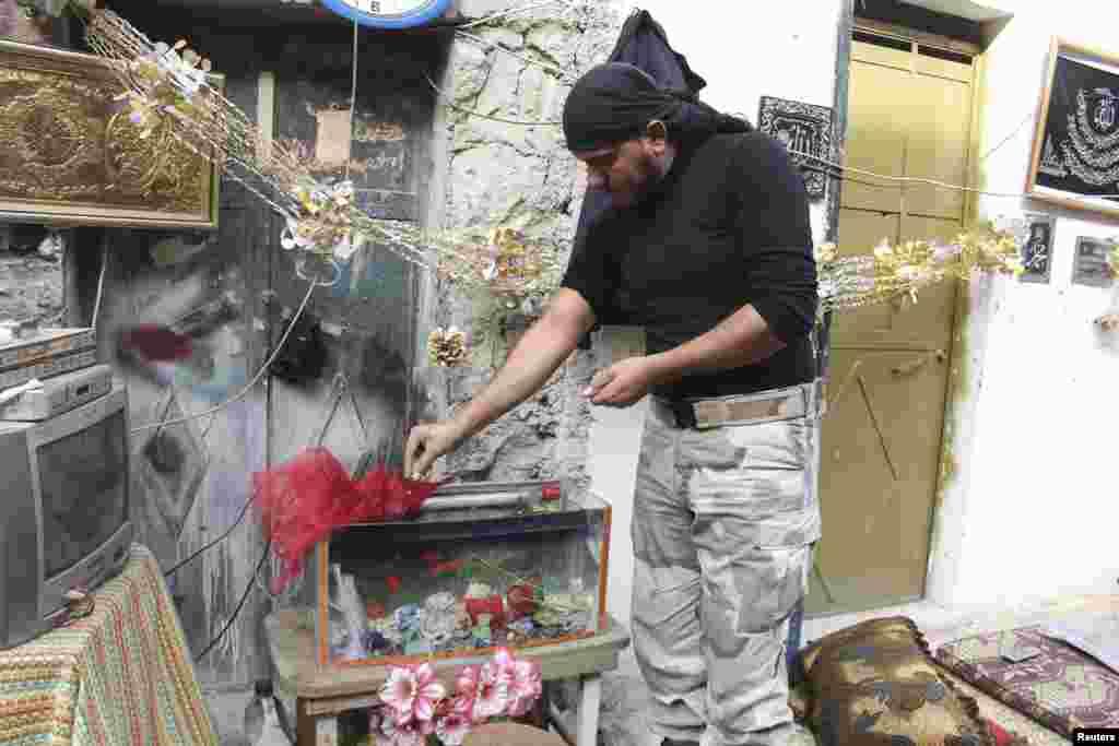 6일 시리아 알레포시의 반군 병사가 어항의 물고기에 먹이를 주고 있다.