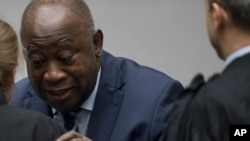 Former Ivory Coast President Laurent Gbagbo greets his legal team as he enters the courtroom of the International Criminal Court in The Hague, Netherlands, Jan. 15, 2019. Judges found Gbagbo and ex-government minister Charles Ble Goude not guilty because of a lack of evidence.