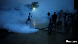 Workers of the Ministry of Public Health and Population fumigate a street during a campaign against mosquito breeding to prevent Zika in Port-au-Prince, Haiti, Sept. 7, 2016.