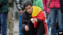 Un homme met une bougie pour les victimes des attentats, Place de la Bourse, Bruxelles, 23 mars 2016.
