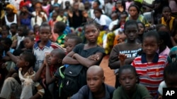Children watch pro-government supporters gathering for an election rally in Bamako, Mali.