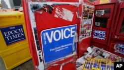 FILE - A rack for copies of The Village Voice is seen among other newspaper drop boxes along a Manhattan sidewalk, Nov. 27, 2013.