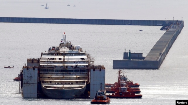 Tug boats push the Costa Concordia ship inside Genoa's port, in northern Italy, where the ship will be broken up for scrap, July 27, 2014.