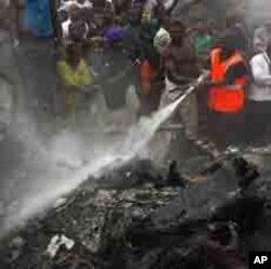'Yan kallo sun taru yayin da 'yan kwana-kwana ke kokarin kashe wutar da ta tashi lokacin da jirgin saman kamfanin Dana Airlines ya fadi a wata unguwar Lagos bayan tasowar shi daga Abuja ranar lahadi 3 Yuni, 2012.