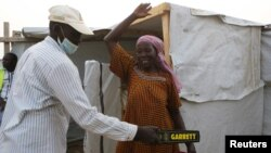 Un agent de sécurité fouille une femme au camp de réfugiés de Minawao à Minawao, au Cameroun, le 15 mars 2016.