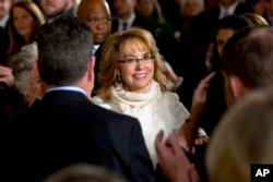 FILE - People applaud former Arizona Rep. Gabby Giffords as she arrives in the East Room of the White House in Washington, to hear President Obama speak about steps his administration is taking to reduce gun violence, Jan. 5, 2016.