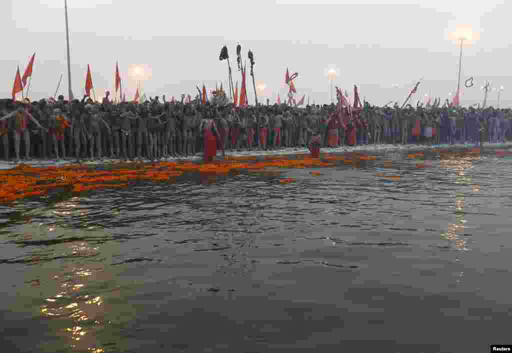 Hindu holymen prepare to take a holy dip during first grand bath of the Kumbh Mela, in the northern Indian city of Allahabad, January 14, 2013.