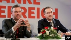 FILE - Norbert Hofer, left, and Heinz-Christian Strache of Austria's anti-migrant and anti-EU Freedom Party attend a news conference in Vienna, Dec. 6, 2016.