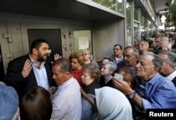 A bank manager tries to explain the situation to hundreds of pensioners queuing outside a National Bank branch in Athens, Greece, July 1, 2015. About one thousand Bank branches around Greece opened on Wednesday to allow pensioners to receive a small part
