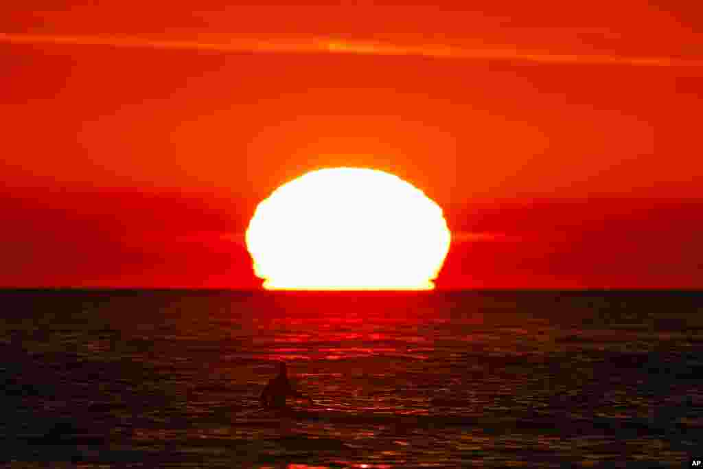 A surfer waits for a wave as the sun sets over the horizon in Pacific Palisades, California.