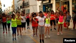 FILE - Youths take part in a Zumba exercise class held near Malaga, southern Spain, July 11, 2013.