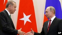 FILE - Russian President Vladimir Putin, right, and Turkish President Recep Tayyip Erdogan shake hands after a news conference in Putin's residence in Sochi, Russia, May 3, 2017.