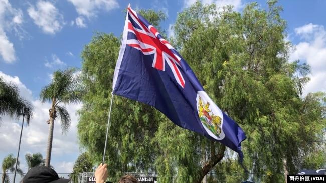 """""""全球反独裁集会""""洛杉矶巴恩斯公园力挺香港活动中,一名男子举着英国国旗"""